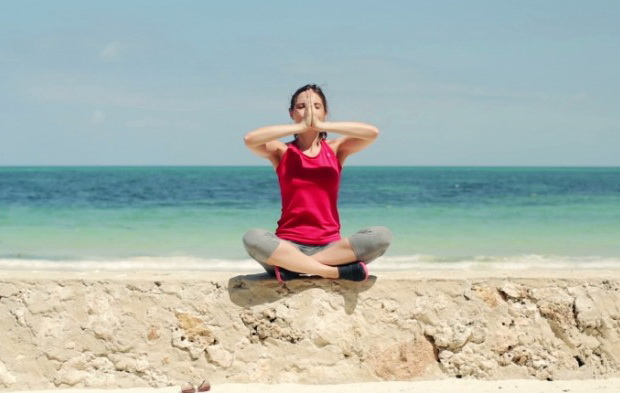 stock-footage-young-beautiful-woman-meditating-by-the-sea-700x393